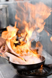 Fire blazes from a frying-pan as a chef flambés a dish